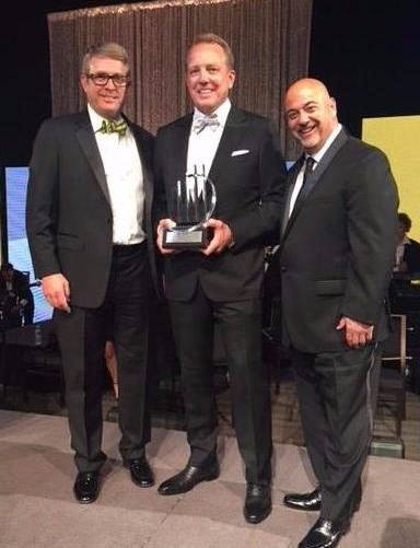 Jon Kinning, COO, Rick Kinning, CEO (holding award), and Marc Paolicelli, CCO.